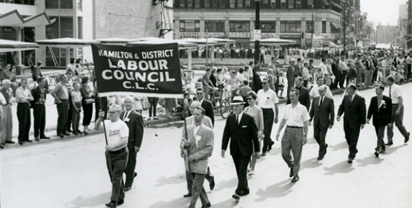 Delegation from the Hamilton & District Labour Council marching west at Market Square. Mayor Victor Kennedy Copps is in the white hat marching behind the banner. King William Street and the Lister building are in the background.