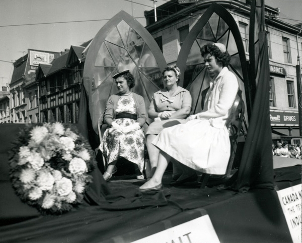 Some ladies riding on an unidentified float during the Labour Day Parade on September 6, 1960. They have just gone past the intersection of King and James Streets and are continuing up James Street.